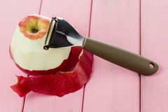 Knife for cleaning fruits and vegetables with apple with peeled skin on a pink background.  stock photos