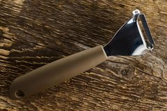 Knife for cleaning vegetables and fruits on a background of rough wooden texture. Cutter for fruits and vegetables stock images