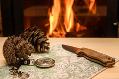 Knife Compass and map lie by the fire. Royalty Free Stock Image