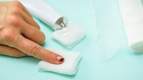 A knife-cut index finger of the left female hand, a tube of ointment and a bandage on a blue table. royalty free stock image
