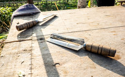 Knife for cut sugar cane on wood table, outdoor street shop Royalty Free Stock Images