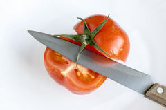 Knife and cut tomato. Knife and slice of fresh tomato on white plate royalty free stock image