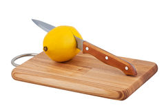 Knife cuts lemon on cutting board. Royalty Free Stock Photos
