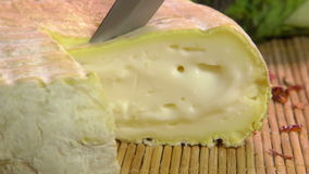 The knife cuts off a piece of Brebis sheep cheese stock footage