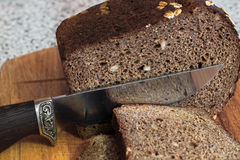 The knife cuts off a piece of brown bread Stock Image