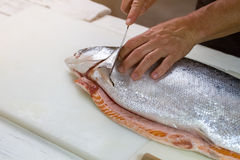 Knife cuts raw fish. Male hands with kitchen knife. Salmon bought in local shop. Product high in protein Stock Photos