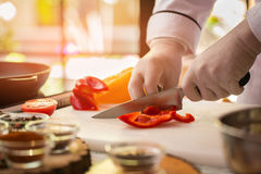 Knife cuts red paprika. Stock Photo