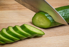 The knife cuts vegetables on a wooden cutting board Stock Images