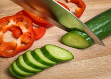 The knife cuts vegetables on a wooden cutting board Stock Photos