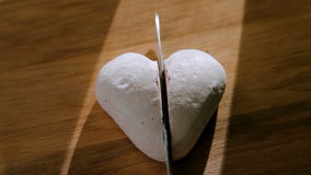 The knife cuts white cookies in the shape of a heart into two halves. Cut white cookies - a symbol of a broken Cerda stock video