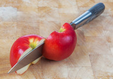 Knife cutting an apple on chopping board Stock Photo