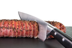 Knife is cutting a big portion of roast pork on a dark slate wit. A knife is cutting a big portion of roast pork on a dark slate, isolated on white with Royalty Free Stock Photos