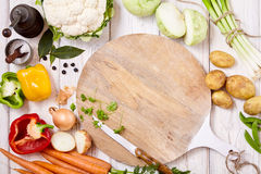 Knife, Cutting Board and Fresh Vegetables on Table Royalty Free Stock Photos