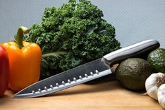 Knife on cutting board with vegetables. Shiny kitchen knife with bell peppers, kale, avocados, and garlic on a cutting board Stock Photos