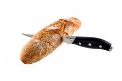 Knife cutting bread loaf isolated on white Royalty Free Stock Photos