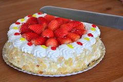 Knife is cutting cream cake with almond. Royalty Free Stock Image