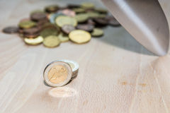 Knife cutting Euro coins. A knife cut a pile of Euro coins with pile of coins in the background Royalty Free Stock Image