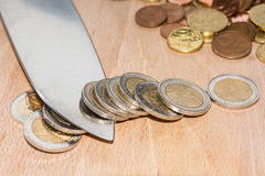 Knife cutting Euro coins. A knife cut a role of Euro coins with pile of coins in the background Royalty Free Stock Photos