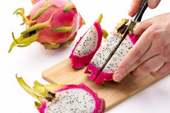 Knife Cutting Half A Pitaya Into Fruit Chips Stock Images