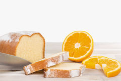 Knife is cutting a lemon cake with some orange fruits on a woode Stock Images