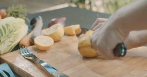 Knife cutting lemon on a wooden board stock video footage