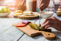 Knife cutting pickled cucumber. Royalty Free Stock Photo