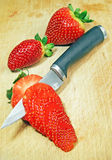 Knife cutting strawberry Stock Images