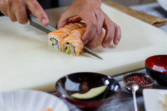 Knife cutting sushi rolls. Stock Photography
