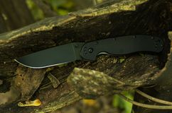 Knife in dark wood. Black knife and dark wood royalty free stock photography