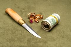Knife and dollars and gold on a green background royalty free stock images