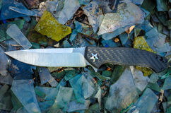 Knife for everyday carrying. Background of broken glass Royalty Free Stock Photo