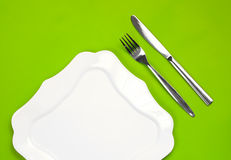 Knife, figured plate and fork on green top view Stock Images