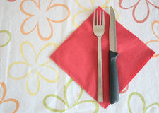 Knife and fork. One knife and a fork over a red paper tissue, on a flower table cloth Royalty Free Stock Photo