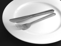Knife and Fork. On a white plate Royalty Free Stock Image