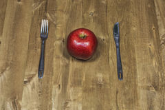 Knife, fork and apple lie on a wooden surface Stock Images