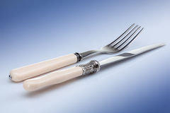 Knife and fork on blue Royalty Free Stock Photos