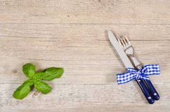 Knife and fork with blue checkered bow on a dinner table Stock Photo