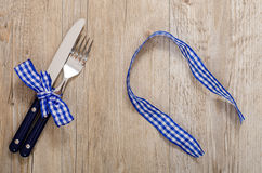 Knife and fork with blue checkered bow Stock Photo