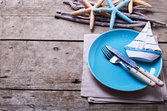 Knife and fork on blue plate and ocean theme decorations on age stock photo