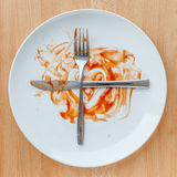 Knife and fork crossed in finish plate and heart shape ketchup, Royalty Free Stock Photography