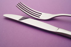 Knife and fork detail over a purple background. Cutlery Stock Images