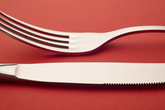 Knife and fork detail over a red background. Cutlery Royalty Free Stock Photography