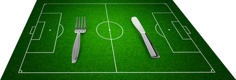 Knife and fork on football field concept Royalty Free Stock Photography