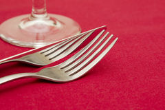 Knife fork and glass on red Royalty Free Stock Photo