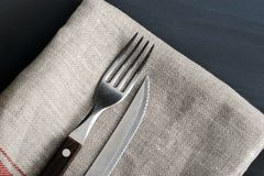 Knife and fork on the linen tablecloth. On wooden table Stock Photo