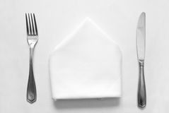 Knife, fork and napkin. In restaurant Royalty Free Stock Photos