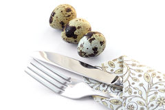 Knife and fork in a napkin with quail eggs. Isolated on a white background Royalty Free Stock Image