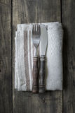 Knife and fork at napkin on wood board Stock Photography