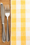 Knife and fork at napkin on wood Stock Photography