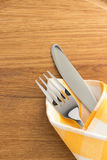 Knife and fork at napkin on wood Royalty Free Stock Photos